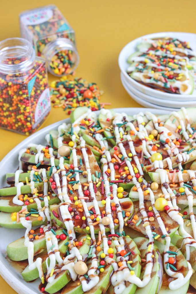 side view of apple dessert nachos loaded on white plate with fall sprinkles