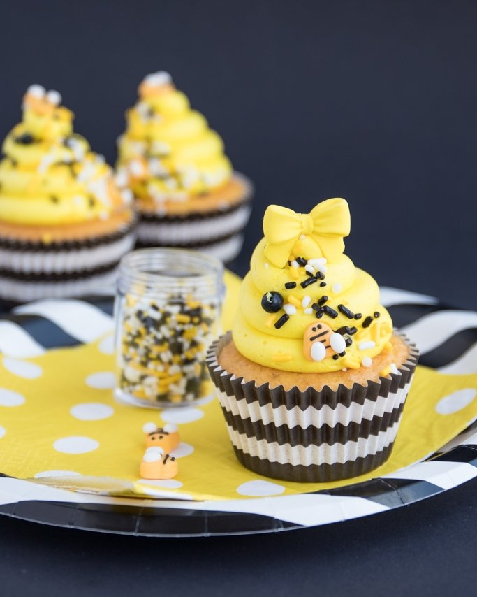 Bee themed party cupcakes with bee hive sprinkles on black striped paper plate and yellow dot napkins