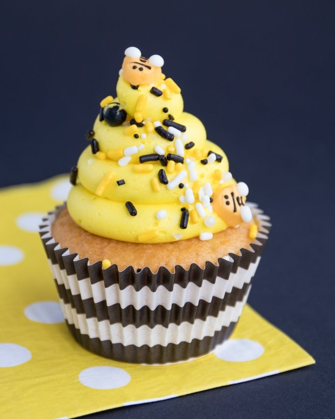 Bee Themed Party Ideas - Bee party cupcakes in black striped greaseproof cupcake liners on yellow dot napkin and black background