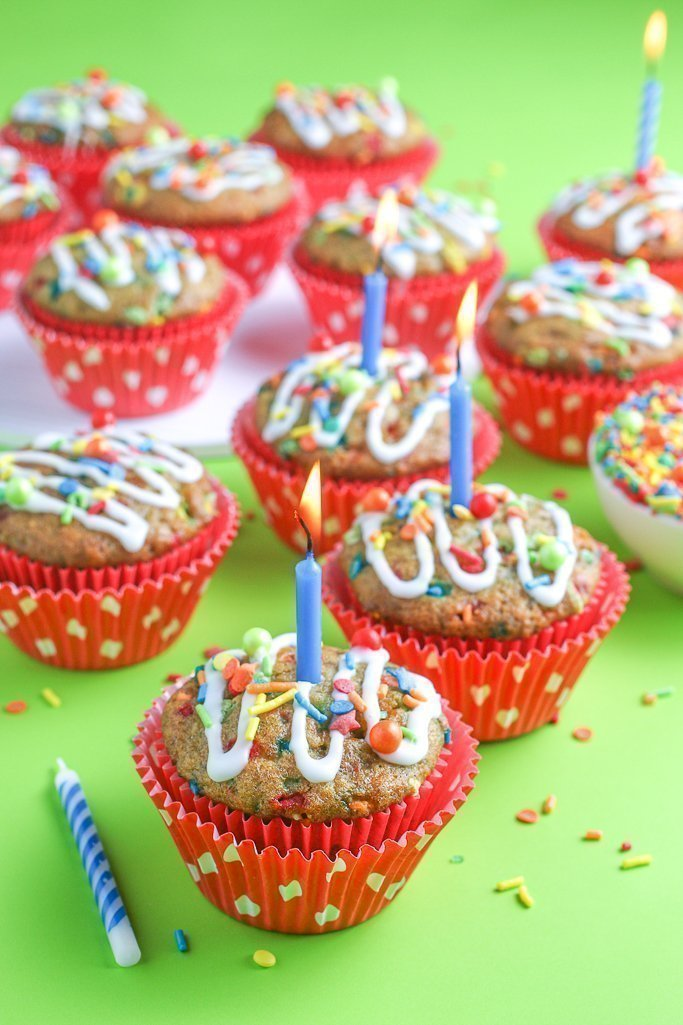 A close up shot of the finished birthday cake muffins with a candle and icing ready to be shared!