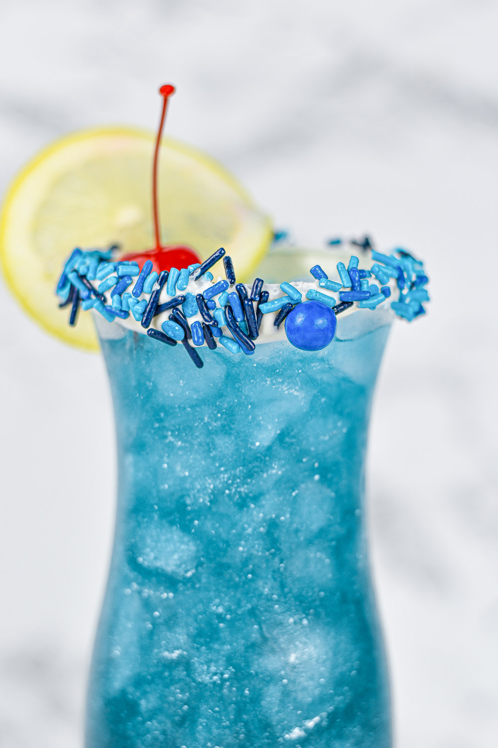 closeup of sprinkle rimmed glass showing glitter filled blue lagoon drink recipe