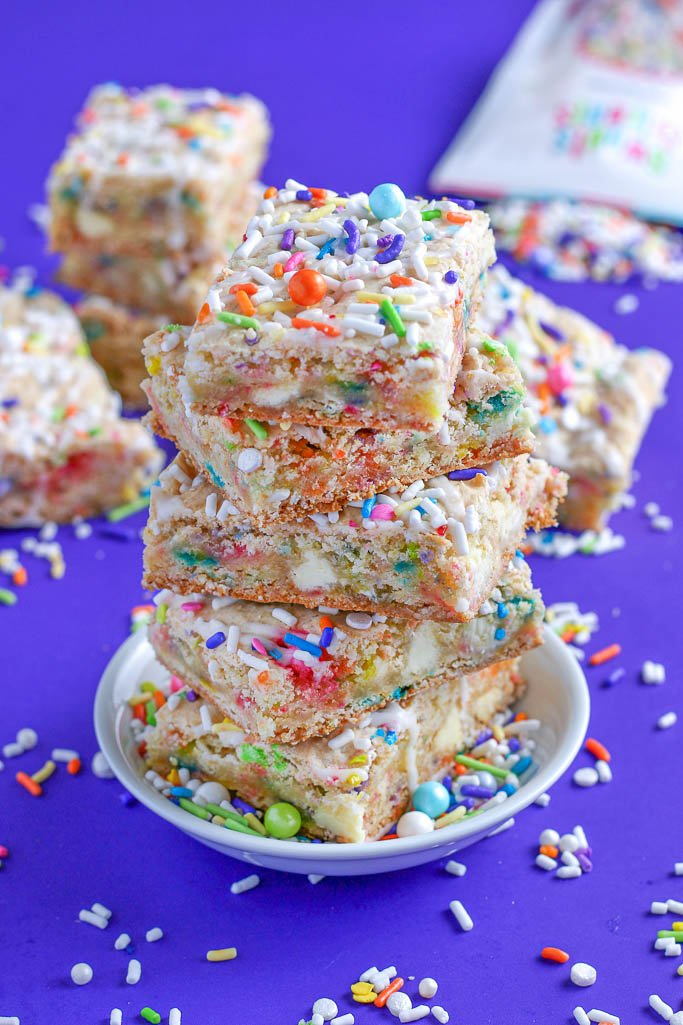 This photo shows the cake batter blondies baked to perfection, cut, and stacked up on a plate.