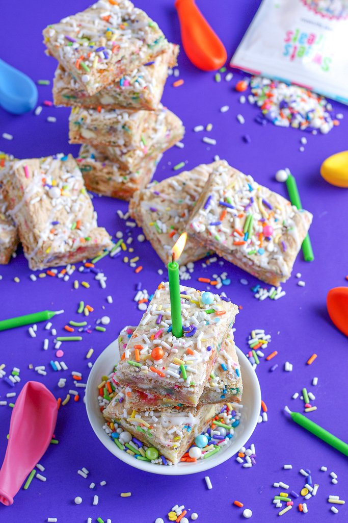 Another look at the finished cake batter blondies stacked up with a candle for celebrating!