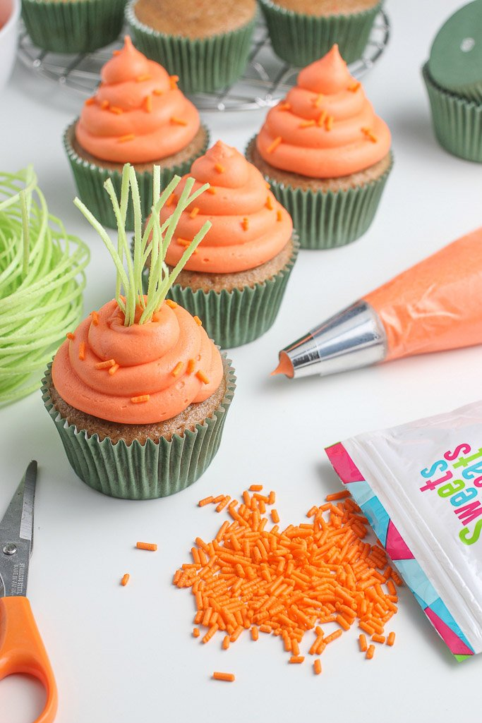 After adding orange sprinkles, we add edible grass tops to our cupcakes so they look even more like delicious little carrots!