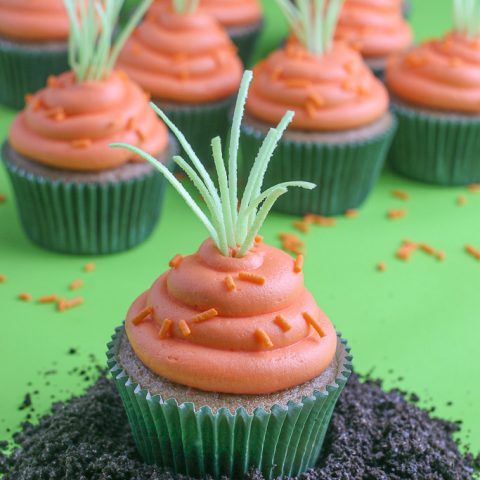 This is a close up of the finished carrot cake cupcakes recipe decorated and sitting in a pile of candy dirt!