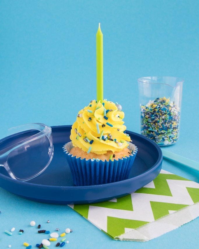 Science Party Cupcakes on navy plate topped with lime candle on blue background
