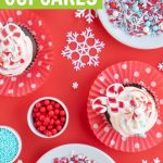 overhead shot of chocolate peppermint cupcakes with peppermint frosting and christmas sprinkles on red background