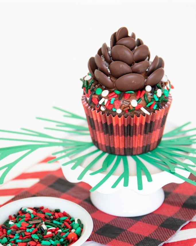 closeup of chocolate pinecone cupcake on white pedestal near lumberjack sprinkles