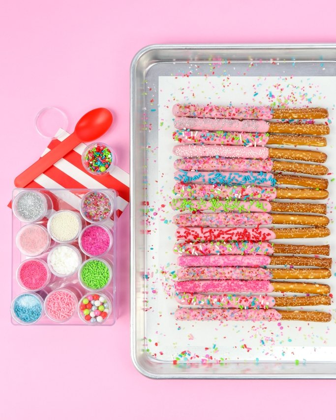 Sprinkle Dipped Christmas Chocolate Covered Pretzel Rods on light pink background with christmas sprinkles