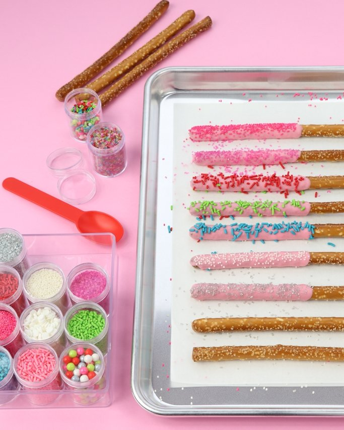 Sprinkled Chocolate Covered Christmas Pretzels on baking sheets with sprinkles