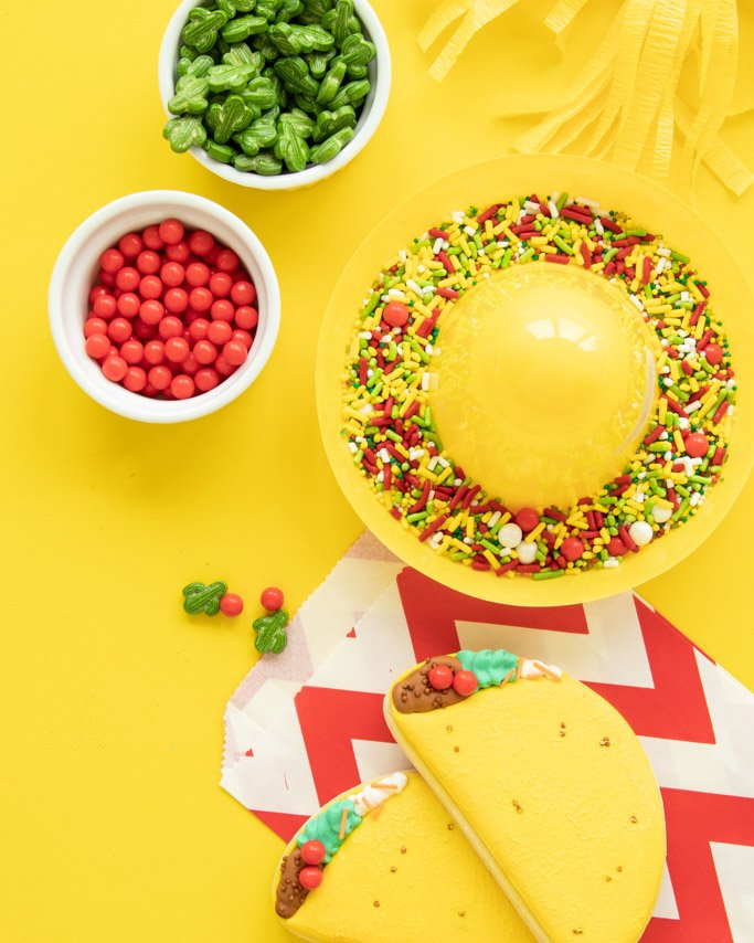 overhead photo of taco cookies and cactus sprinkles on yellow background