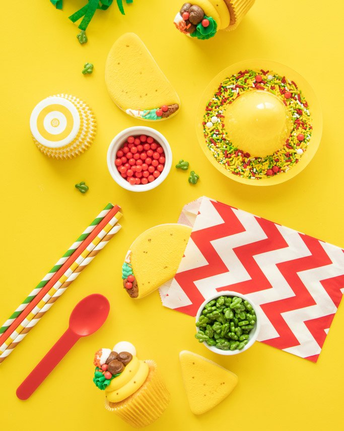 overhead photo of cinco de mayo party supplies and taco cookie and taco cupcakes