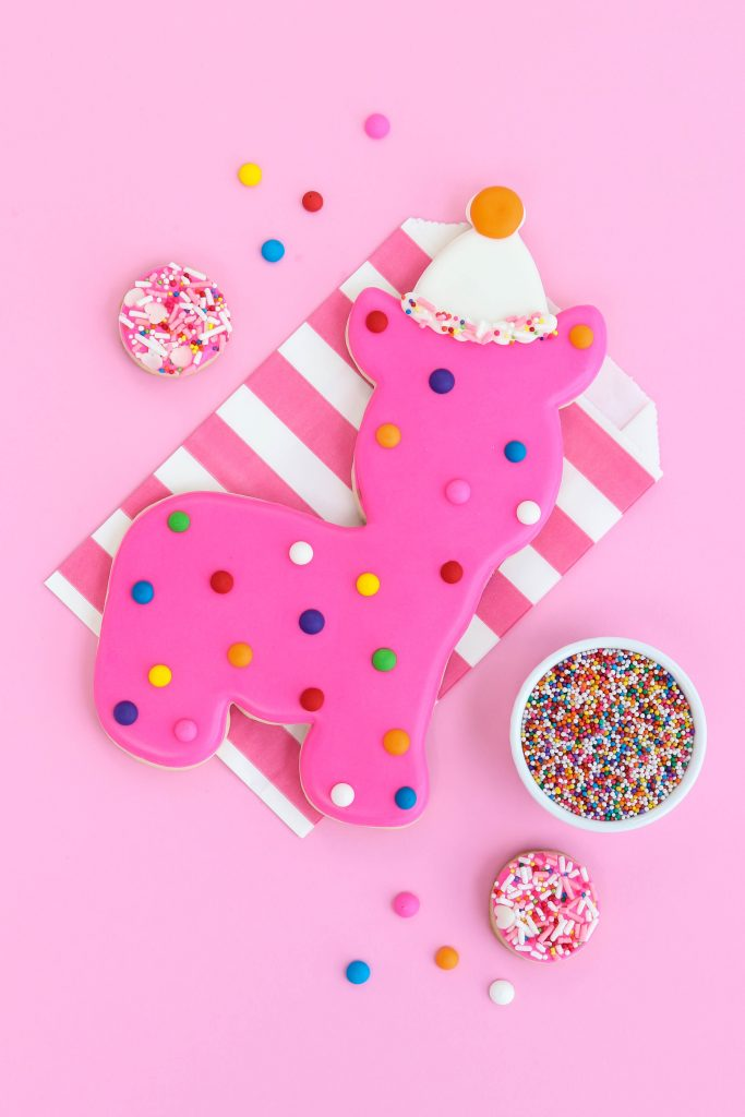 Circus Animal Cookies Party - Huge dot circus animal cookie on pink striped paper favor bag with sprinkle cookies around