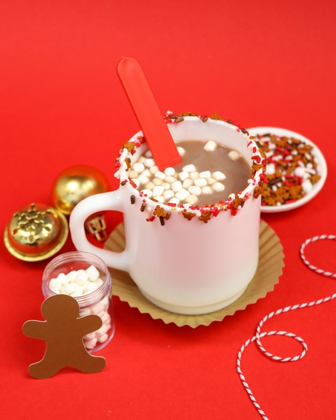 Cocoa & Cookies Christmas Party Ideas - Hot cocoa with reindeer food sprinkle rim on mugs on red background