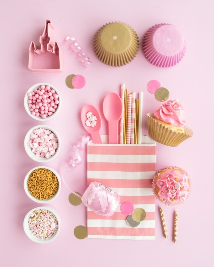 Pink and gold party supplies collage on light pink background