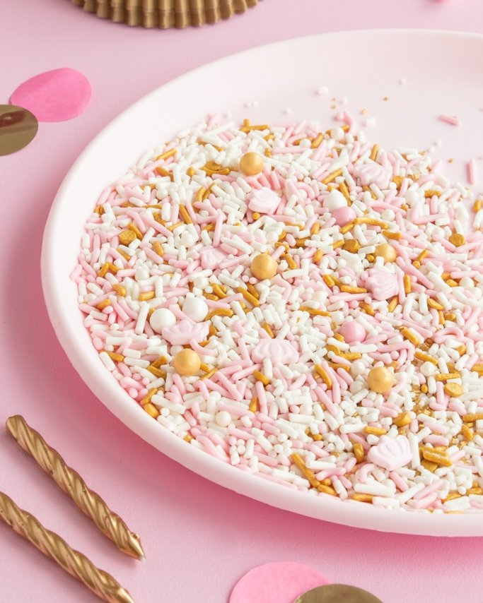Pink and gold party sprinkles with crown candy sprinkles on white plate and light pink background