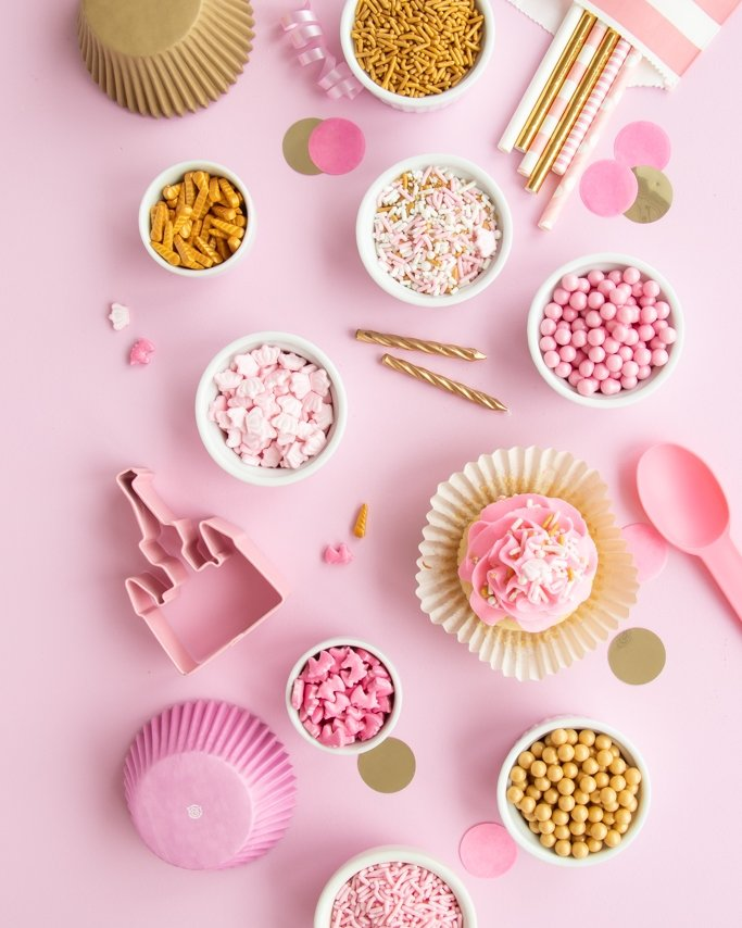 Pink and gold party supplies laid out on light pink background - gold sprinkles, light pink party supplies