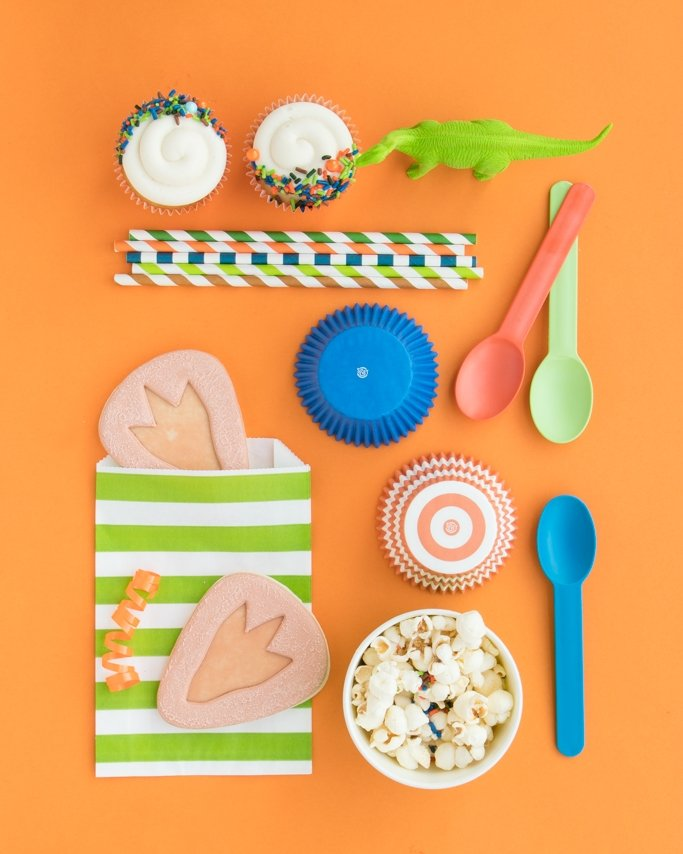 Dinosaur Party Supplies with cookies, cupcakes, and popcorn on orange background