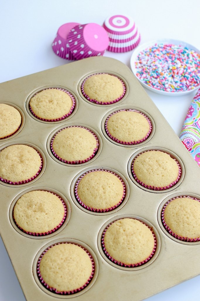 Baked vanilla cupcakes fresh from the oven in pink greaseproof cupcake liners