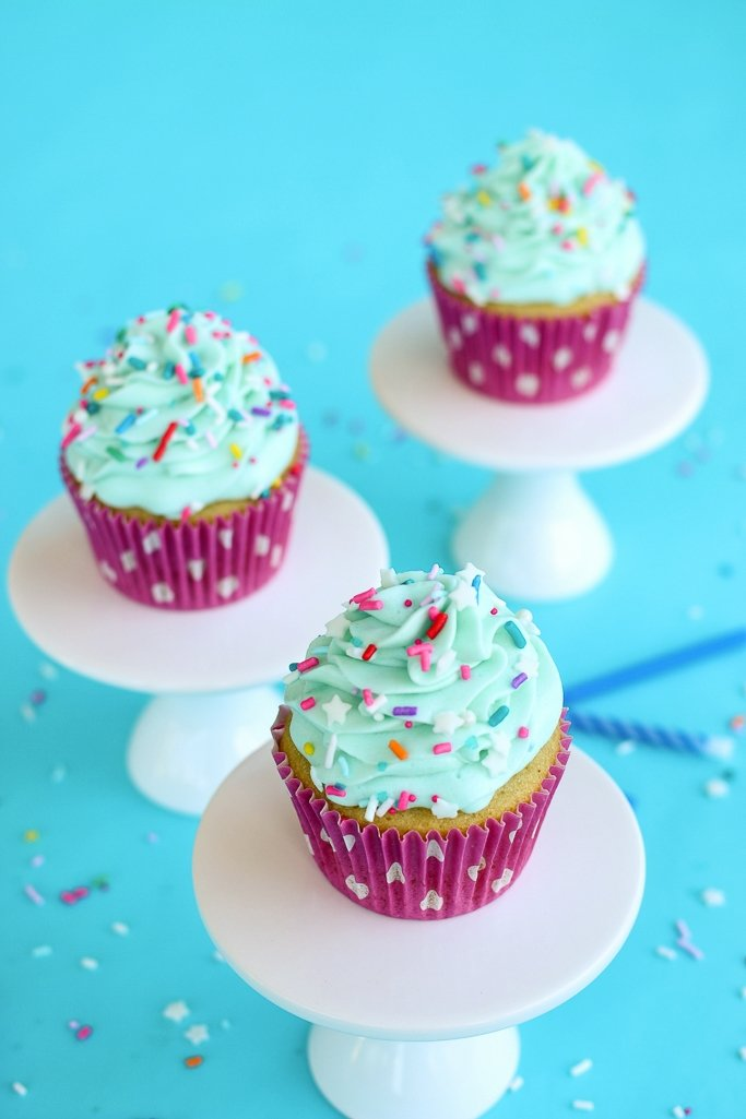 Three cupcakes on pedestals made from a vanilla cupcake recipe.