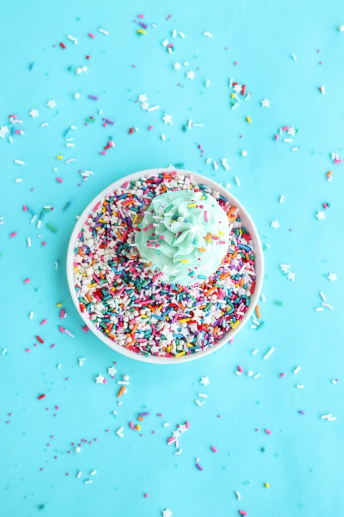 Overhead view of colorful sprinkles surrounding a single vanilla cupcake on a plate.