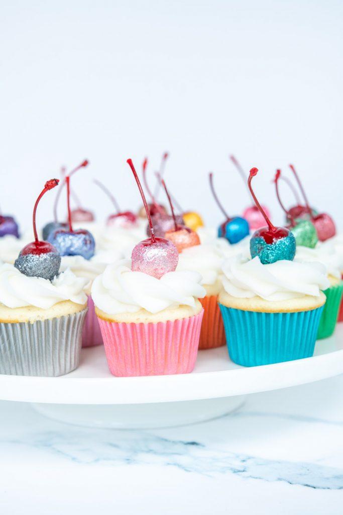 cake plate full of glitter cherry topped cupcakes