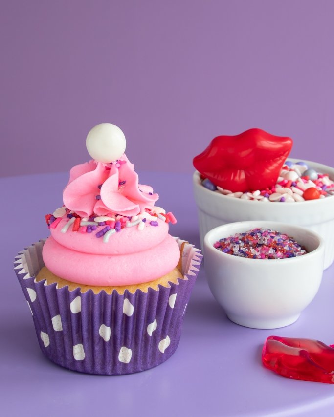 Pink & Purple Valentine Cupcakes with sprinkle ruffle and dot purple cupcake liners on purple background
