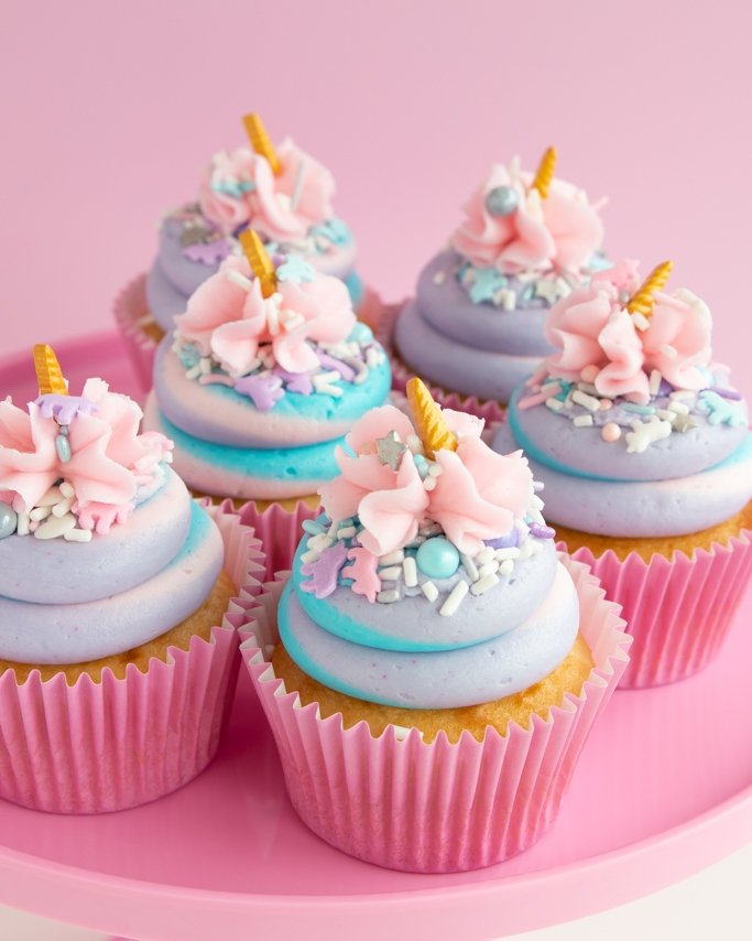 Unicorn Cupcakes topped with unicorn sprinkles and in light pink cupcake liners on pink cake plate