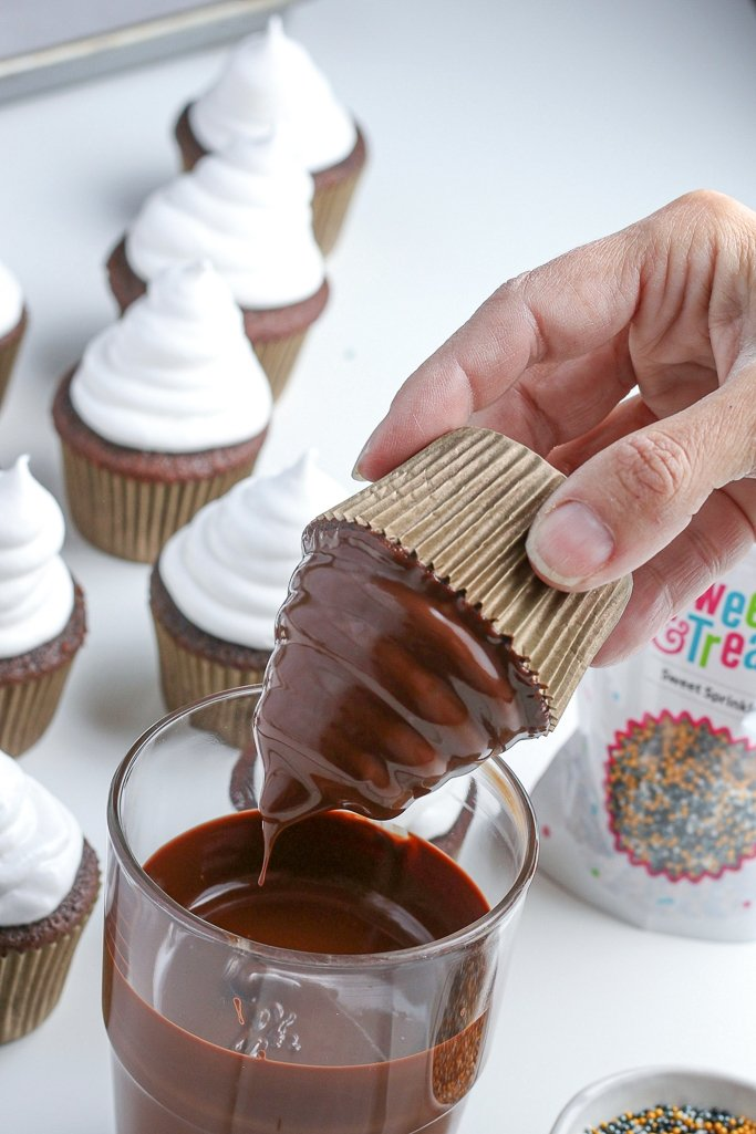 photo of chocolate cupcakes with frosting being dipped into chocolate coating