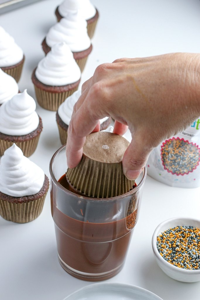photo of chocolate hi hat cupcakes being dipped in melted chocolate coating