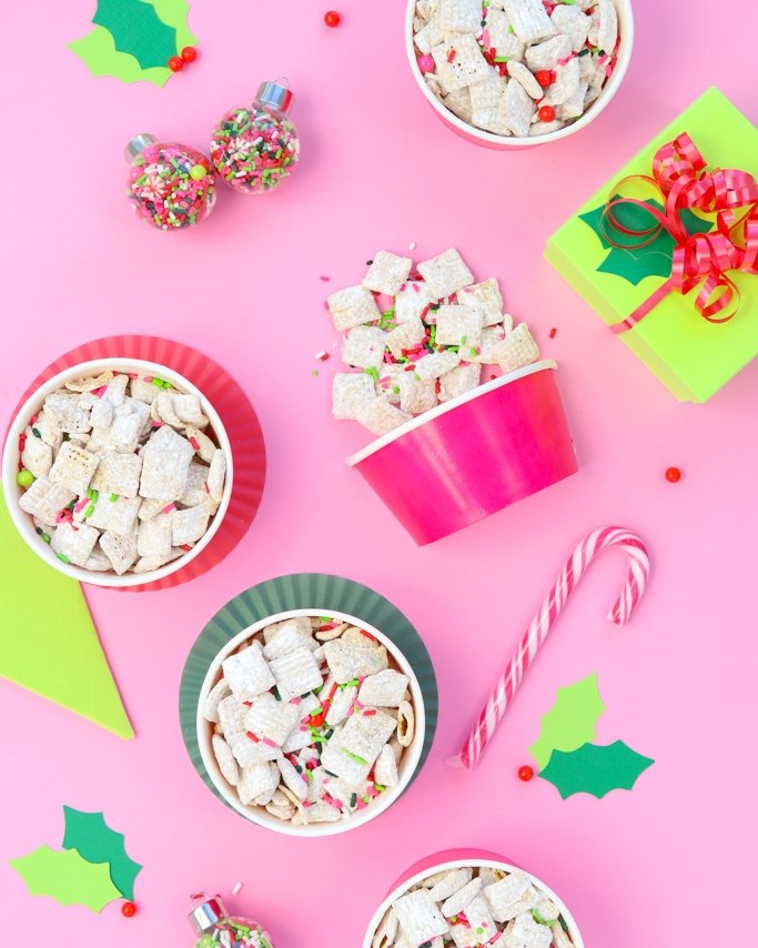White Chocolate Christmas Puppy Chow Recipe - Christmas Muddy Buddies in treat cups on pink background and sprinkle ornaments around