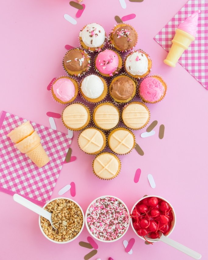 Ice Cream Cone Cupcake Cake on light pink background with sprinkles table confetti