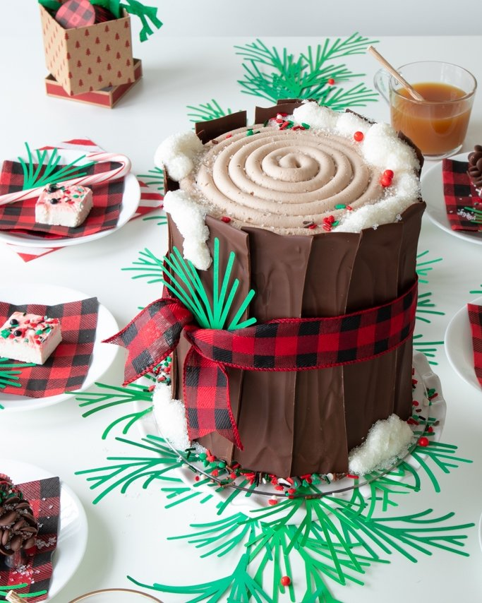 tree stump cake with buffalo plaid ribbon, peppermint fudge, and apple cider all around