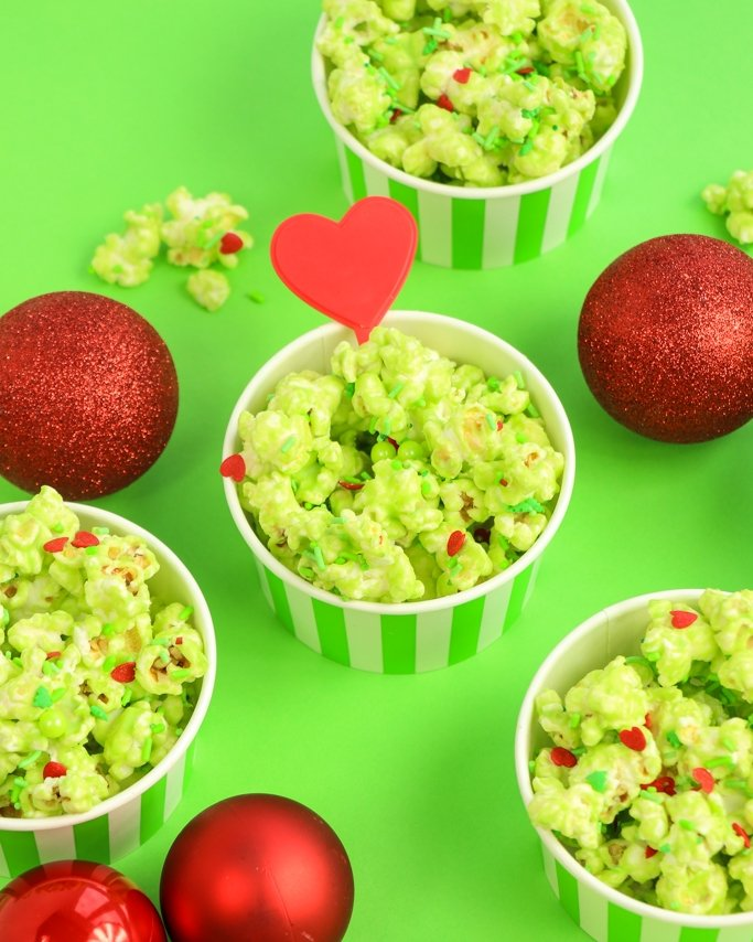 Grinch Popcorn in ice cream bowls on lime green background.