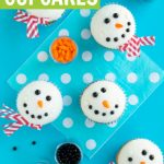 melting snowman cupcakes on blue background