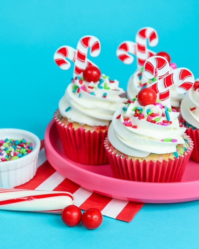 Raspberry Buttercream Cupcakes on pink plate and blue background with Christmas sprinkles