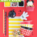 Mickey Mouse Party Supplies with sprinkles, cupcake liners, and straws on red background