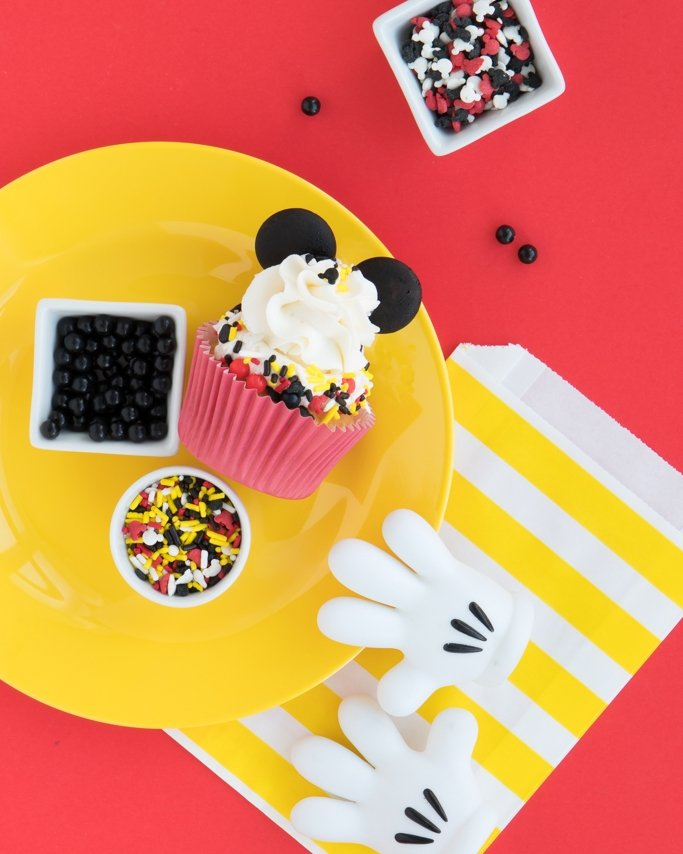 Mickey Mouse Party Ideas - Mickey Mouse theme party supplies and sprinkles on yellow plate and red background