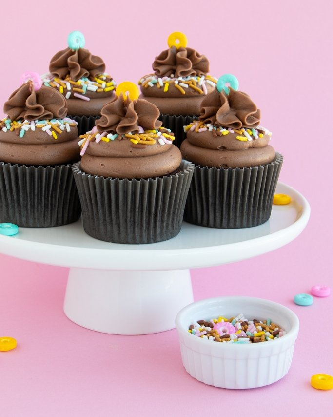 Mocha cupcakes on white cake plate with donut sprinkles