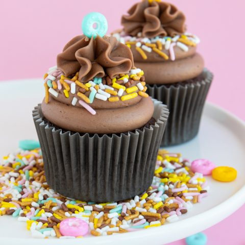 Mocha cupcakes topped with mocha frosting on plate of donut sprinkles
