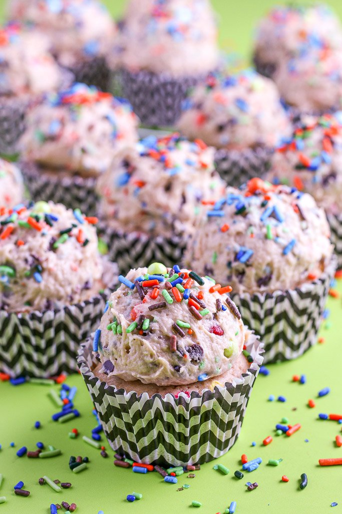 A close up view of a single monster cookie cupcakes with cookie dough ready to be eaten.