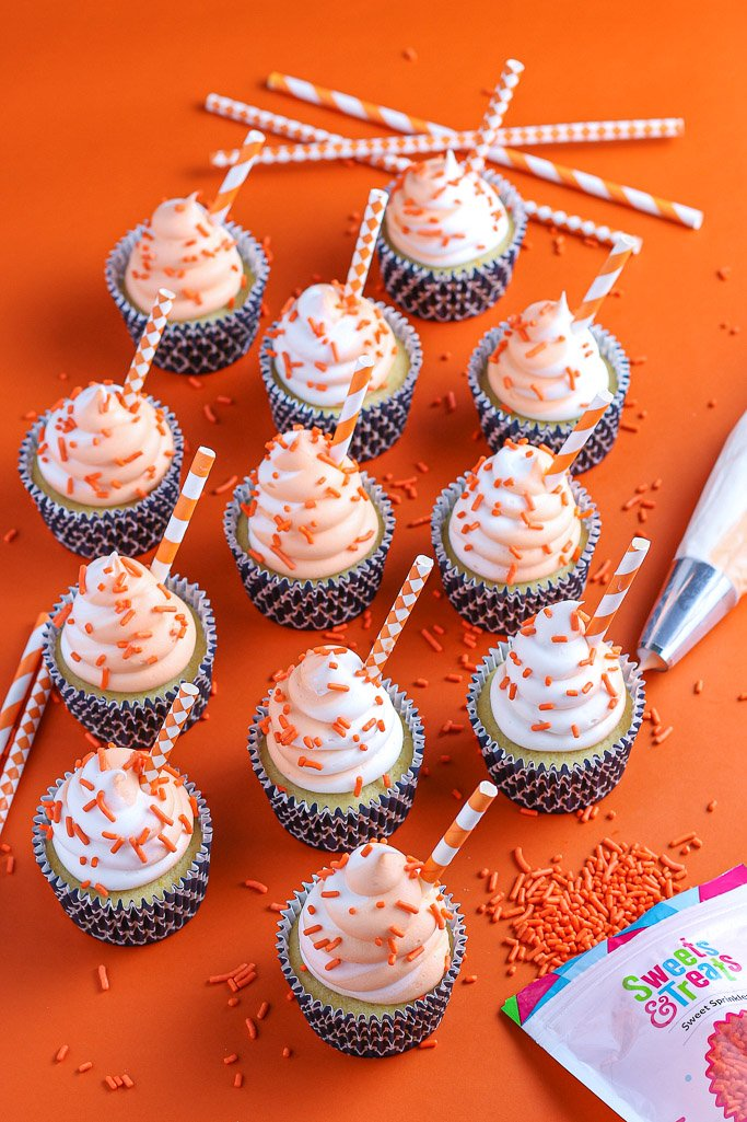 A close up view of a finished and decorated orange cream cupcake ready to be shared.
