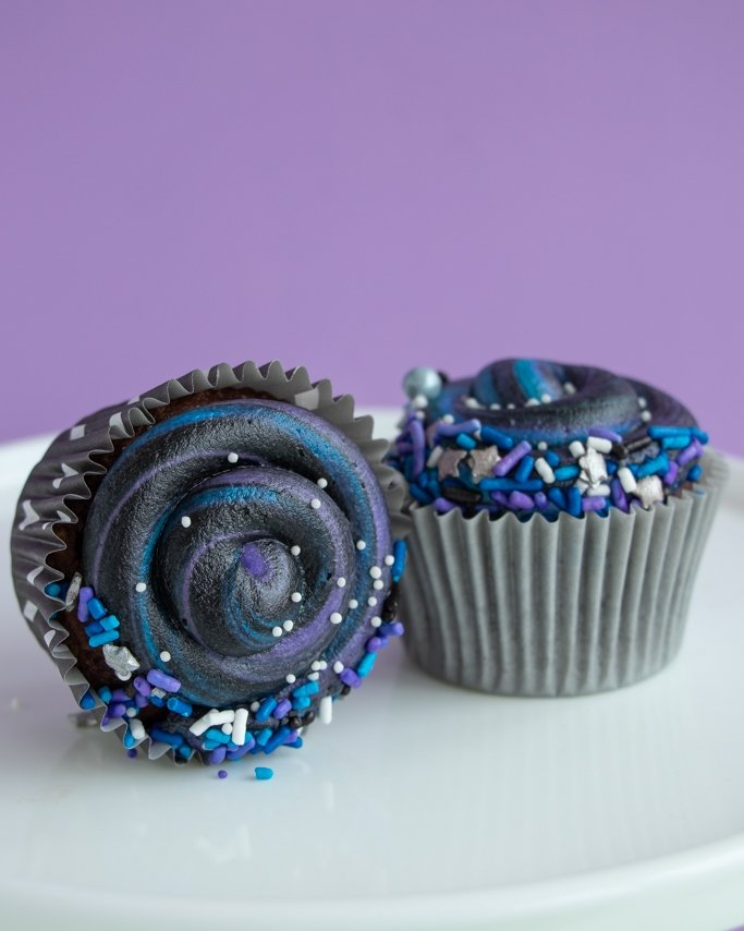 Swirly Galaxy Cupcakes on cake plate and purple background