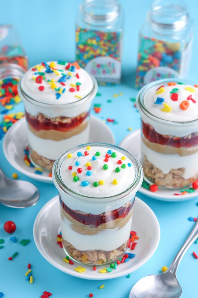front view of three different peanut butter and jelly parfaits decorating with back to school sprinkles