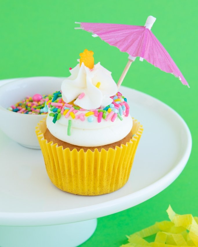 Luaua party cupcake with tropical sprinkles on white cake plate