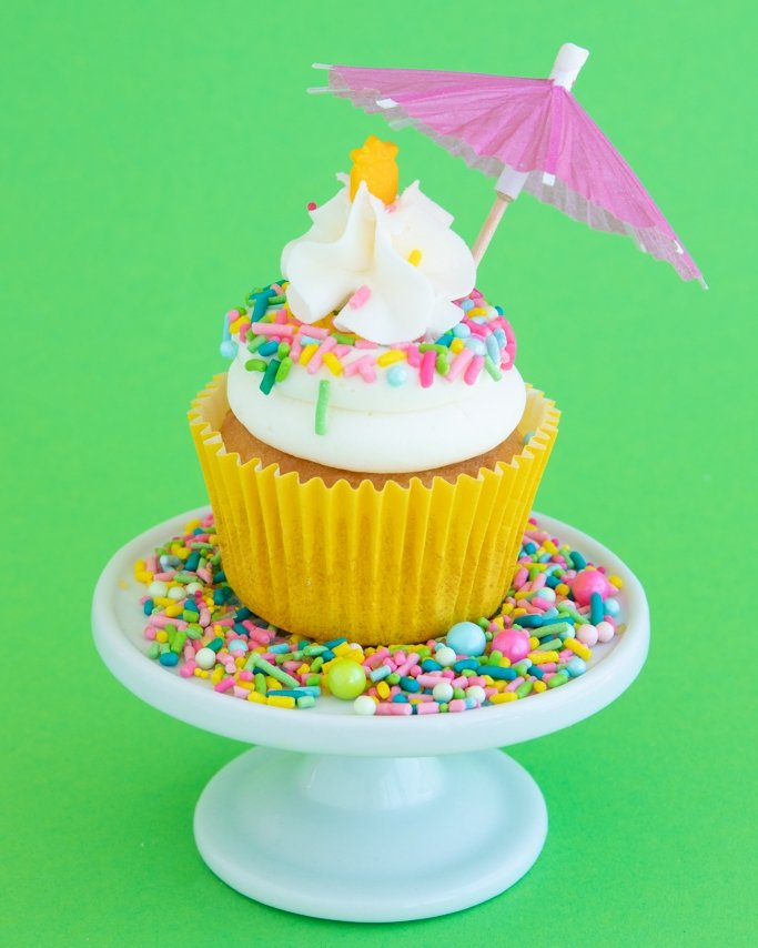 Pina Colada Cupcakes on white plate of tropical sprinkles