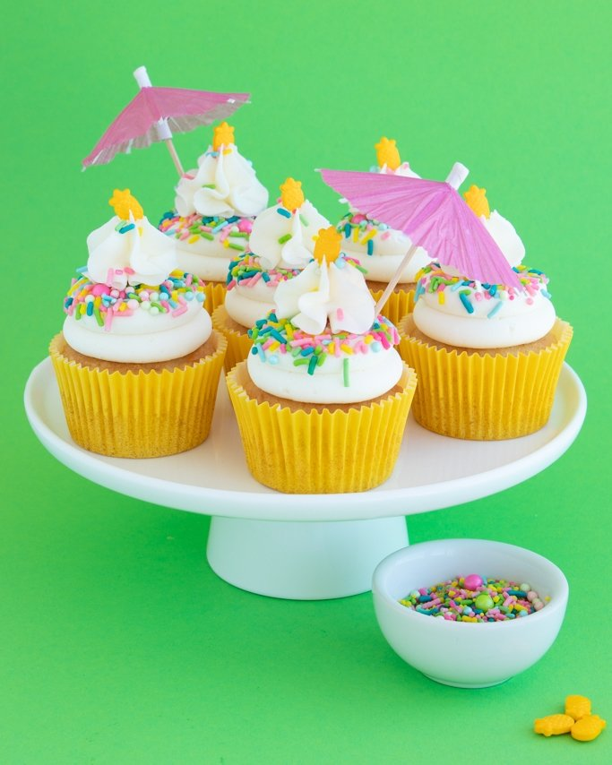 Pina Colada Cupcakes Recipe - pineapple cupcakes with coconut frosting and sprinkles on white cake plate