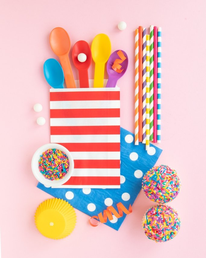 Assorted rainbow party supplies, rainbow sprinkles on cupcakes, and rainbow baking supplies on pink background