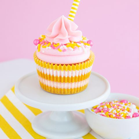 Pink lemonade cupcakes on white cupcake plate