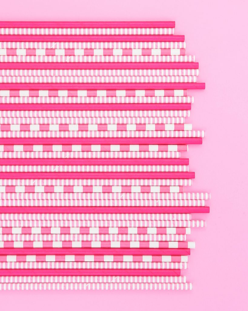 Circus Animal Cookies Party - Striped, Solid, and pinstripe pink paper straws all in a row on a pink background